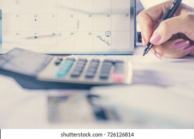 business woman hand calculating her monthly expenses with credit card, idea for shopping online , debt and payment concept background ,selective focus on deadline calendar note