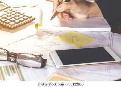 business woman hand calculating her monthly expenses during tax season with some bills ,financial graph and smart phone  on desk