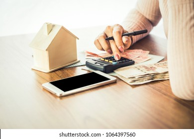 business woman hand counting money paper currency with smart phone,house model and calculator on desk, planing to buy or rent home concept