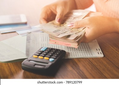 business woman hand counting money paper currency with saving account book and calculator on table