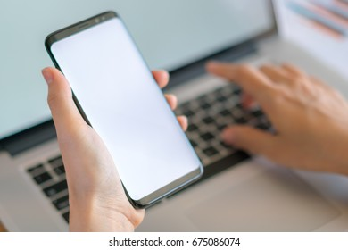Business woman hand with Financial charts and mobile phone over laptop on the table
