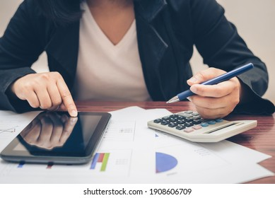 business woman hand hold pen and using calculator and pointing on tablet mobile technology for analysis and budget financial accounting with growth statistics chart and graph on paper work.