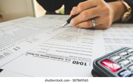 Business woman hand hold pen fill in the details on the tax forms paper in business concept.