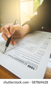 Business woman hand hold pen fill in the details on the tax forms paper in business concept