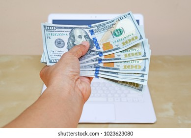business woman hand holding American dollar currency on white laptop on wood desk.