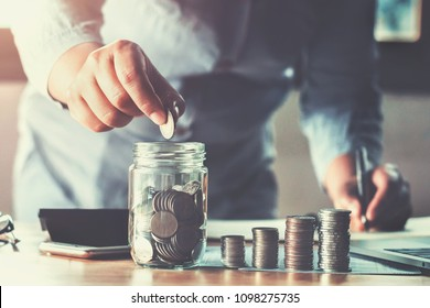 business woman hand holding coins puting into glass. concept saving money finance and accounting