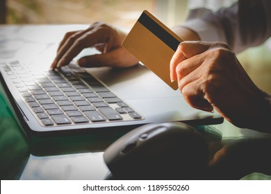 Business woman hand holding credit card and typing on laptop computer keyboard for online shopping and payment at home office. Business financial technology, e banking,e commerce concept.Vintage tone