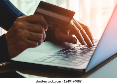 Business woman hand holding credit card, using and typing on laptop computer keyboard  for online shopping and payment at home office. e business, e commerce, internet banking concept.