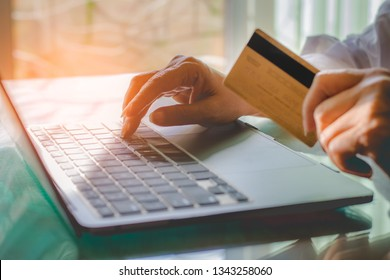 Business woman hand holding golden credit card and using laptop computer for online payment and shopping at home.Digital marketing,internet banking concept.