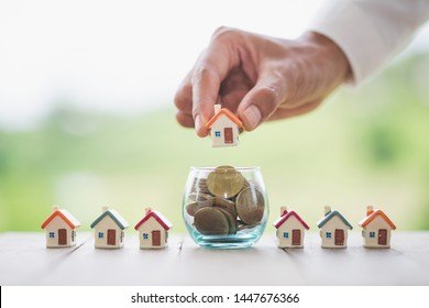 Business woman hand holding house On a coin in a glass bottle.Concept of saving money to buy a house Saving money, investing in real estate.Home trading business.