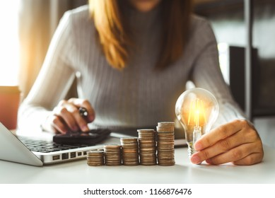 business woman hand holding lightbulb with using smartphone and calculator to calculate and money stack. idea saving energy and accounting finance in morning light