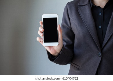 Business woman hand holding mobile phone. Business woman working on a digital tablet. Business woman show cell telephone in black dressed suit on white background, Close up hand man use mobile phone
