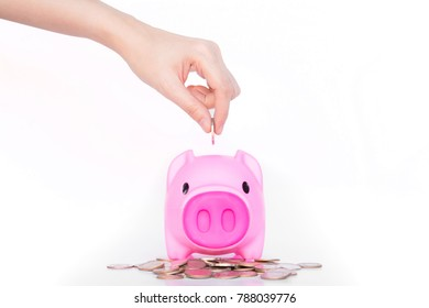 Business woman hand inserting coin in piggy bank on white background.