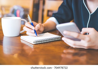 Business woman hand is on a notepad with a pen on a wooden desk in the office.On her table is a cup of coffee and a mobile phone.