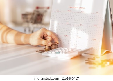 business woman hand putting coin To stack of coins that including calculator, calendar on wooden table