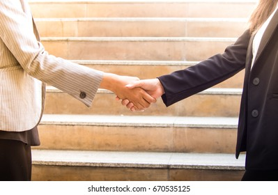 Business woman hand shaking with business partner. Business concept.