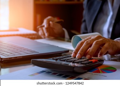 Business woman hand using calculator and counting about budget,income, profit of the company, plan to write  checkbook,work on laptop computer,data graph paper and notebook .paycheck concept.