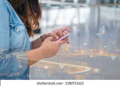 Business woman hand using smart phone on double exposure of smart city with wifi connection technology of internet of things. Business technology lifestyle concept of new generation of nomad workers.
