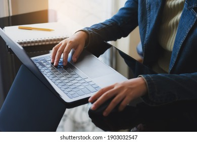 Business woman hand using wireless mouse, work on laptop computer with notepad and pen on the desk at home office. Online learning or home school concept.