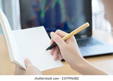 Business woman hand working in a computer and writing with a pen at a notepad