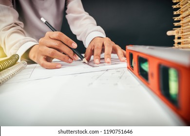 business woman hand working and laptop with on on architectural project at construction site at office desk in office warm colours sun light