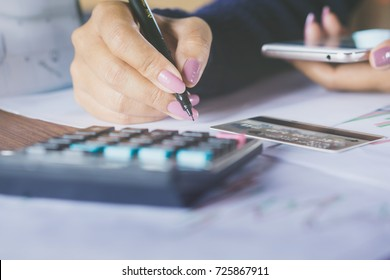 business woman hand writing and calculating her monthly expenses with blur background credit card , another hand holding smart phone