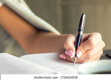 Business woman hand is writing in notepad with pen at cafe.
