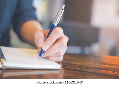 Business woman hand writing on a notebook with a pen in the office