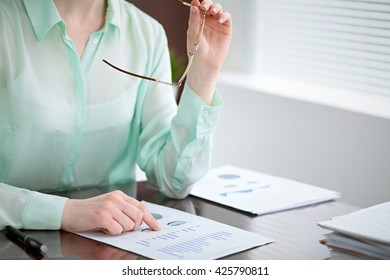 Business woman hands in a green blouse sitting at the desk in the office and examine the financial results , the right window .