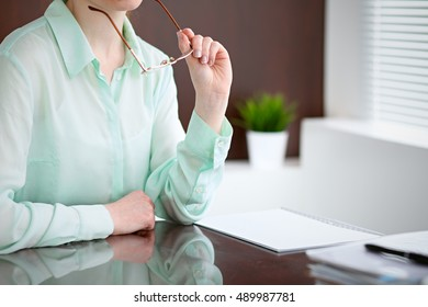 Business woman hands in a green blouse sitting at the desk in the office and holding glasses, the right window . She is thinking about the business problems, the successes, the concepts