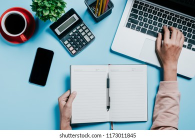 Business woman hands with pen writing notebook  on office desk table close up. Business concept.