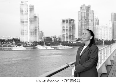 business woman or happy cute girl with smiling face in grey jacket, has red manicure on ship deck viewing sea, ocean water with sailing boat on cloudy sky background, traveling and tourism
