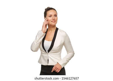 Business woman in a happy mood talking on a smartphone in a white jacket with her hair in a bun