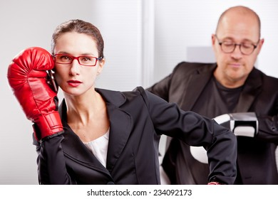 a business woman has been interrupted by a telephone call on her mobile while she was performing a box match with a business man that now is waiting for her to quit that call and keep on boxing