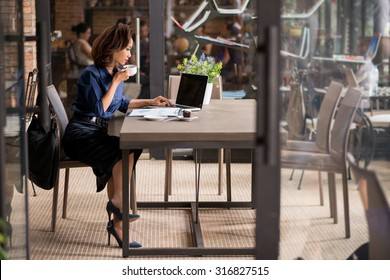 Business woman having cup of coffee and working on laptop in a cafe