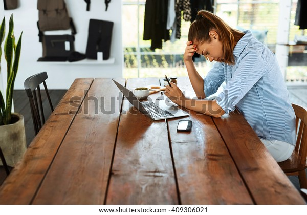 Business Woman Having Headache While Working Using Laptop Computer. Stressed And Depressed Girl Touching Her Head, Feeling Pain While Sitting At Wooden Table At Cafe. Work Failure Concept