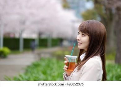 Business woman having tea on the cherry tree street