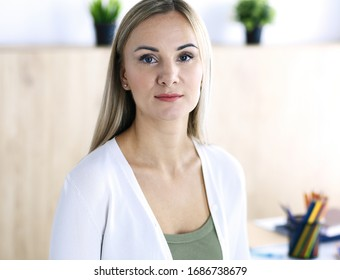 Business woman headshot while working with computer at the desk in modern office. Designer looks beautiful in white casual clothes. Business people concept