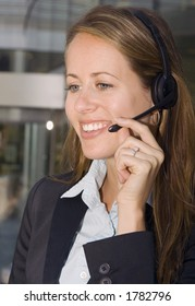 A business woman is helping customers on the phone.