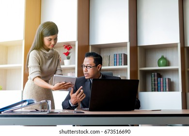 Business woman and her boss meeting with tablet at office.