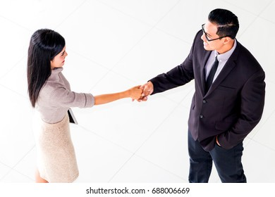 Business woman and her boss shaking hands during meeting at office.