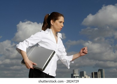 Business woman and her laptop. blue skies in the background.