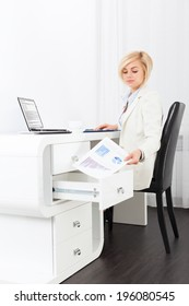 business woman hide document in desk box, businesswoman sitting in modern bright office, concept of dirty accounting corruption