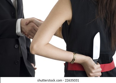 business woman hiding a knife while handshaking an associate depicting an intention to back stab