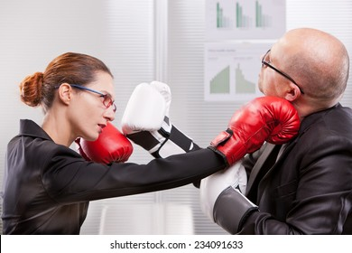 business woman hitting a business man in a box match with a right jab