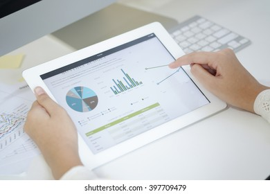 business woman hold analyzing financial chart on tablet