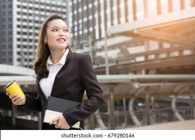 Business woman hold coffee cup and book notepad happy smile on something imaginary  look to success ready to work on what we love. concept working woman.