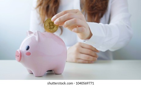 business woman hold pink piggy bank with bitcoin