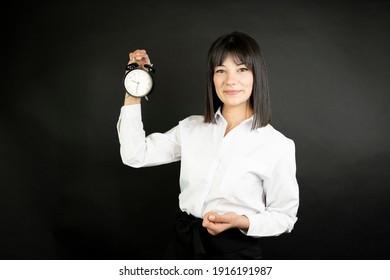 Business woman holding alarm clock.