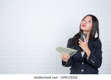 Business woman holding banknote, cash separately, white brick wall Made gestures with sign language.